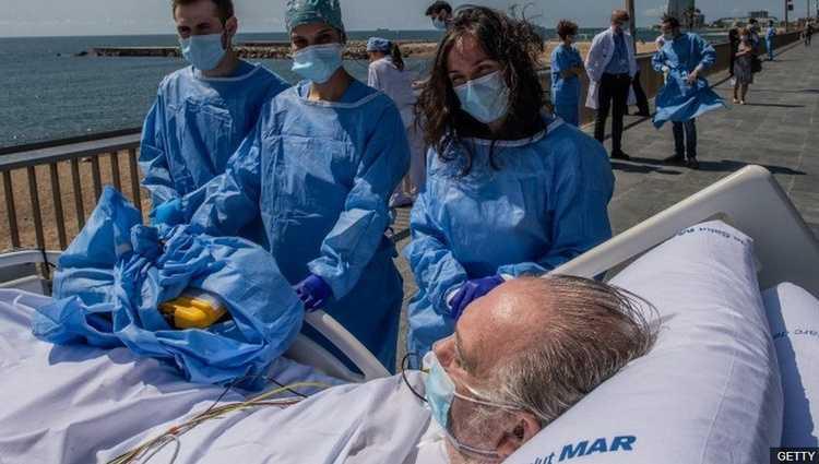ბარსელონაში კოვიდ 19-ით ინფიცირებულს ექიმები პლაჟზე ასეირნებენ
